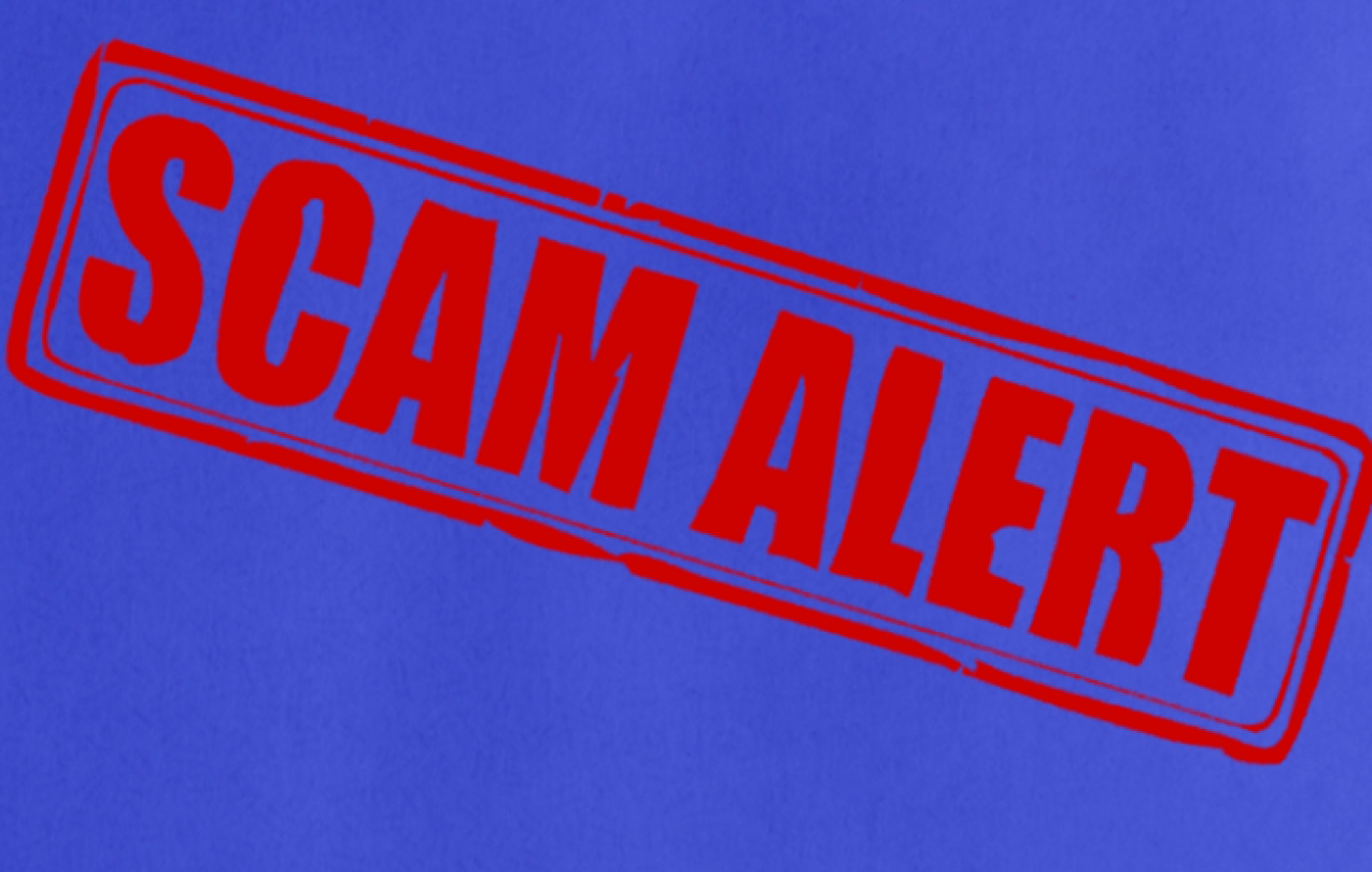 "Red ""SCAM ALERT"" stamp on a blue background"