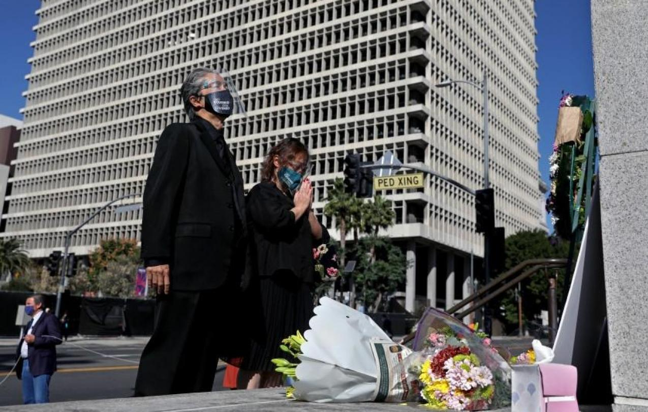 In this undated photo, court interpreter Nao Ikeuchi, left, and wife Yoshimi Shirata attend a vigil to honor two court interpreters at Los Angeles Superior Court who died recently of COVID-19.(Gary Coronado / Los Angeles Times)