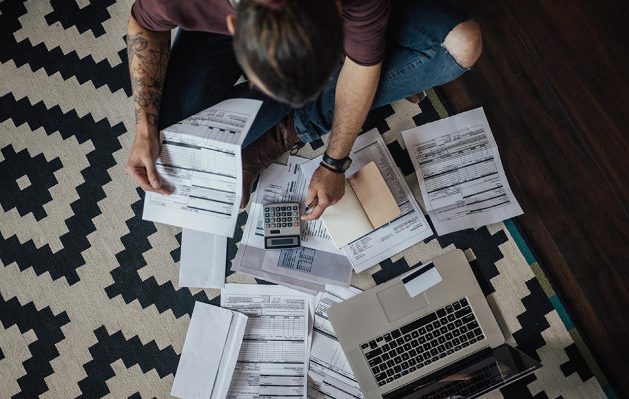 Man, sitting on floor, calculates bills